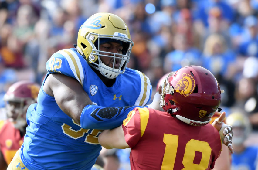PASADENA, CALIFORNIA - NOVEMBER 17: Osa Odighizuwa #92 of the UCLA Bruins gets his hands in the face of JT Daniels #18 of the USC Trojans during the first half at Rose Bowl on November 17, 2018 in Pasadena, California. (Photo by Harry How/Getty Images)