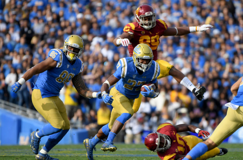 PASADENA, CALIFORNIA - NOVEMBER 17: Joshua Kelley #27 of the UCLA Bruins runs with Devin Asiasi #86 during the second quarter in a 34-27 UCLA win at Rose Bowl on November 17, 2018 in Pasadena, California. (Photo by Harry How/Getty Images)