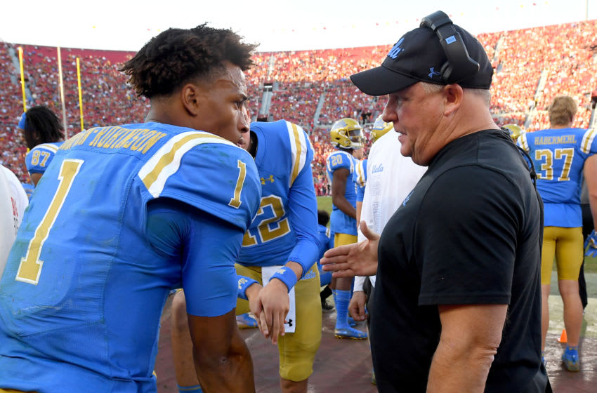 LOS ANGELES, CA - NOVEMBER 23: Head coach Chip Kelly talks with quarterback Dorian Thompson-Robinson #1 as quarterback Austin Burton #12 of the UCLA Bruins looks on on the bench during the game against the USC Trojans at the Los Angeles Memorial Coliseum on November 23, 2019 in Los Angeles, California. (Photo by Jayne Kamin-Oncea/Getty Images)