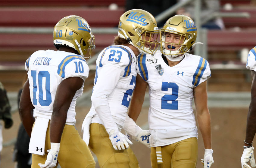 PALO ALTO, CALIFORNIA - OCTOBER 17: Kyle Philips #2 of the UCLA Bruins is congratulated by Chase Cota #23 and Demetric Felton #10 after he scored a touchdown against the Stanford Cardinal at Stanford Stadium on October 17, 2019 in Palo Alto, California. (Photo by Ezra Shaw/Getty Images)