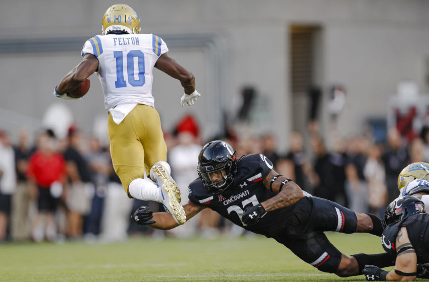 CINCINNATI, OH - AUGUST 29: Demetric Felton #10 of the UCLA Bruins leaps as Darrian Beavers #27 of the Cincinnati Bearcats attempts the tackle at Nippert Stadium on August 29, 2019 in Cincinnati, Ohio. (Photo by Michael Hickey/Getty Images)