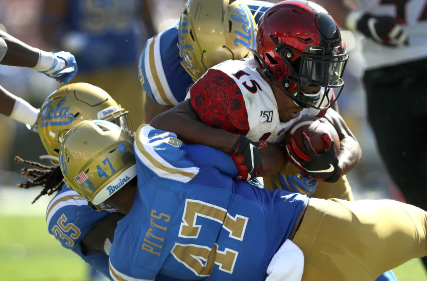 LOS ANGELES, CALIFORNIA - SEPTEMBER 07: Shea Pitts #47 and Carl Jones #35 of the UCLA Bruins tackle Jordan Byrd #15 of the San Diego State Aztecs during the second half of a game on September 07, 2019 in Los Angeles, California. (Photo by Sean M. Haffey/Getty Images)