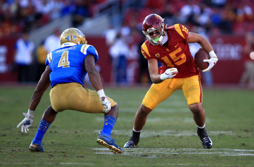 LOS ANGELES, CALIFORNIA - NOVEMBER 23: Drake London #15 of the USC Trojans runs for extra yards as Stephan Blaylock #4 of the UCLA Bruins defends during the second half of a game at Los Angeles Memorial Coliseum on November 23, 2019 in Los Angeles, California. (Photo by Sean M. Haffey/Getty Images)
