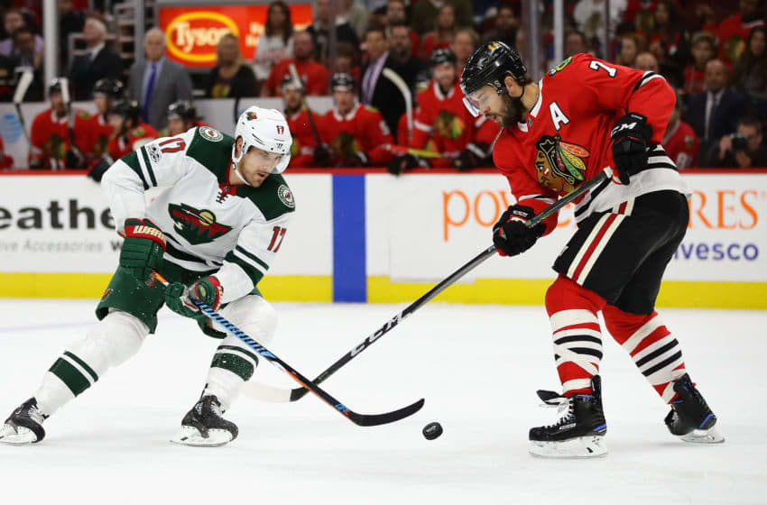 CHICAGO, IL - OCTOBER 12: Marcus Foligno #17 of the Minnesota Wild controls the puck under pressure from Brent Seabrook #7 of the Chicago Blackhawks at the United Center on October 12, 2017 in Chicago, Illinois. (Photo by Jonathan Daniel/Getty Images)