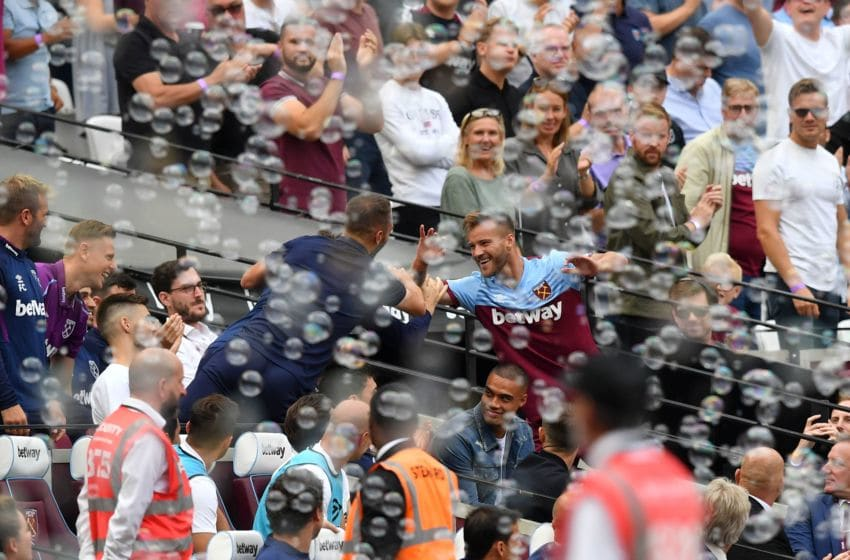 West Ham United's Ukrainian striker Andriy Yarmolenko (R) celebrates scoring their second goal by high-fiving a member of his team in teh stands during the English Premier League football match between West Ham United and Norwich City at The London Stadium, in east London on August 31, 2019. (Photo by Ben STANSALL / AFP) / RESTRICTED TO EDITORIAL USE. No use with unauthorized audio, video, data, fixture lists, club/league logos or 'live' services. Online in-match use limited to 120 images. An additional 40 images may be used in extra time. No video emulation. Social media in-match use limited to 120 images. An additional 40 images may be used in extra time. No use in betting publications, games or single club/league/player publications. / (Photo credit should read BEN STANSALL/AFP via Getty Images)