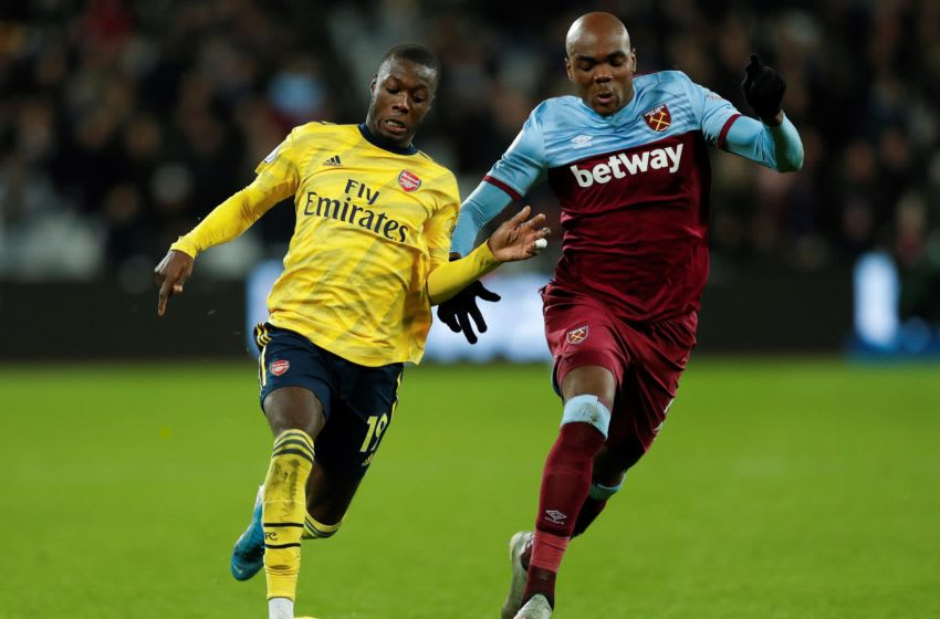 Arsenal's French-born Ivorian midfielder Nicolas Pepe (L) vies with West Ham United's Italian defender Angelo Ogbonna during the English Premier League football match between West Ham United and Arsenal at The London Stadium, in east London on December 9, 2019. (Photo by Adrian DENNIS / AFP) / RESTRICTED TO EDITORIAL USE. No use with unauthorized audio, video, data, fixture lists, club/league logos or 'live' services. Online in-match use limited to 120 images. An additional 40 images may be used in extra time. No video emulation. Social media in-match use limited to 120 images. An additional 40 images may be used in extra time. No use in betting publications, games or single club/league/player publications. / (Photo by ADRIAN DENNIS/AFP via Getty Images)