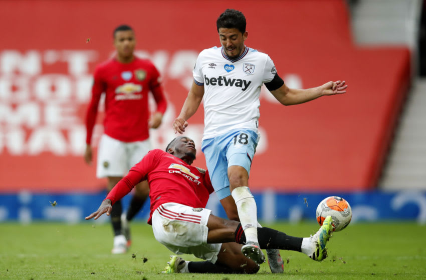MANCHESTER, ENGLAND - JULY 22: Pablo Fornals of West Ham United and Aaron Wan-Bissaka of Manchester United clash during the Premier League match between Manchester United and West Ham United at Old Trafford on July 22, 2020 in Manchester, England. Football Stadiums around Europe remain empty due to the Coronavirus Pandemic as Government social distancing laws prohibit fans inside venues resulting in all fixtures being played behind closed doors. (Photo by Clive Brunskill/Getty Images)