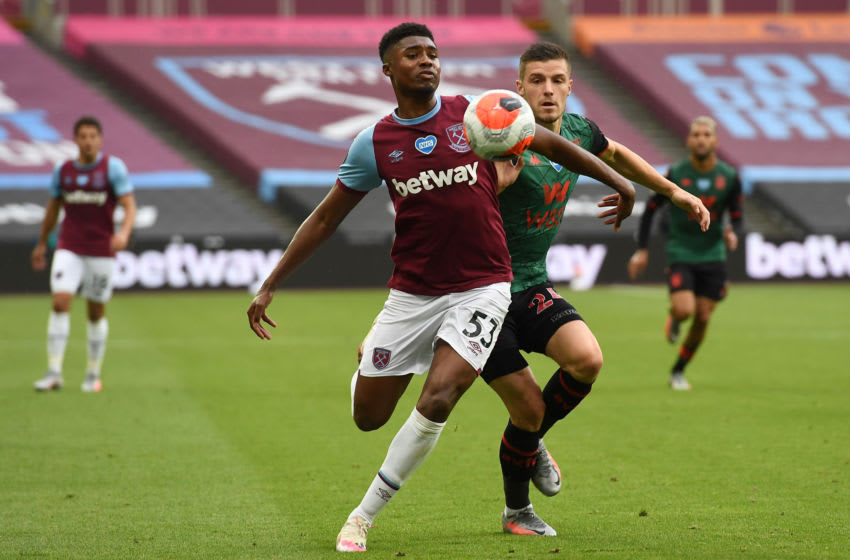 LONDON, ENGLAND - JULY 26: Ben Johnson of West Ham United competes for the ball with Frederic Guilbert of Aston Villa during the Premier League match between West Ham United and Aston Villa at London Stadium on July 26, 2020 in London, England. Football Stadiums around Europe remain empty due to the Coronavirus Pandemic as Government social distancing laws prohibit fans inside venues resulting in all fixtures being played behind closed doors. (Photo by Andy Rain/Pool via Getty Images)