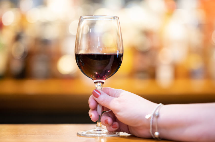 A woman holds a glass of red wine. (Photo by Matthew Horwood/Getty Images)