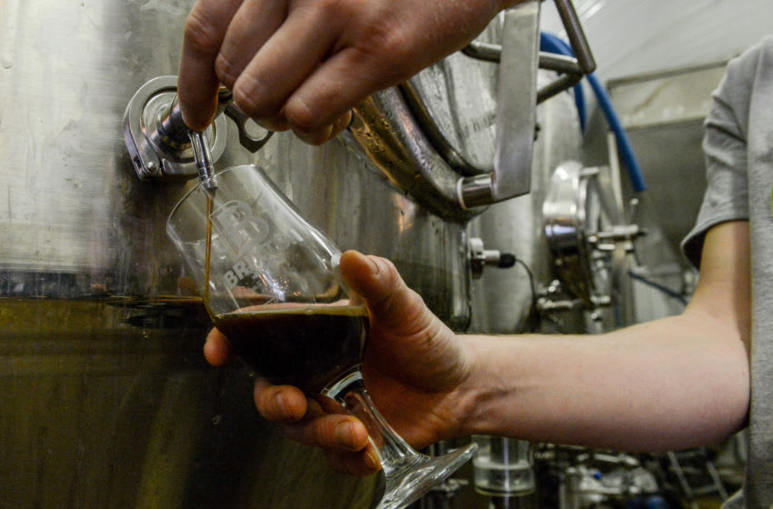 Brewer Sam Jory, 24, takes a sample of Windrush Stout, (Photo by Chris Ratcliffe/Getty Images)