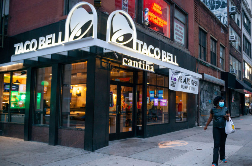 NEW YORK, NEW YORK - JULY 30: A woman wearing a mask walks past Taco Bell Cantina as the city continues Phase 4 of re-opening following restrictions imposed to slow the spread of coronavirus on July 30, 2020 in New York City. The fourth phase allows outdoor arts and entertainment, sporting events without fans and media production. (Photo by Alexi Rosenfeld/Getty Images)