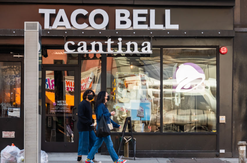 NEW YORK, NEW YORK - MARCH 21: Two people wearing masks walk by a Taco Bell Cantina in Chelsea on March 21, 2021 in New York City. After undergoing various shutdown orders for the past 12 months the city is currently in phase 4 of its reopening plan, allowing for the reopening of low-risk outdoor activities, movie and television productions, indoor dining as well as the opening of movie theaters, all with capacity restrictions. (Photo by Noam Galai/Getty Images)