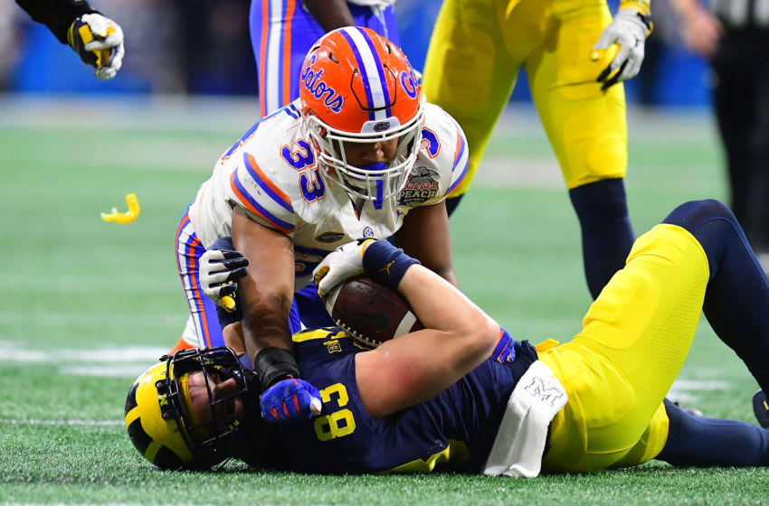 ATLANTA, GEORGIA - DECEMBER 29: Zach Gentry #83 of the Michigan Wolverines is tackled by David Reese II #33 of the Florida Gators in the third quarter during the Chick-fil-A Peach Bowl at Mercedes-Benz Stadium on December 29, 2018 in Atlanta, Georgia. (Photo by Scott Cunningham/Getty Images)