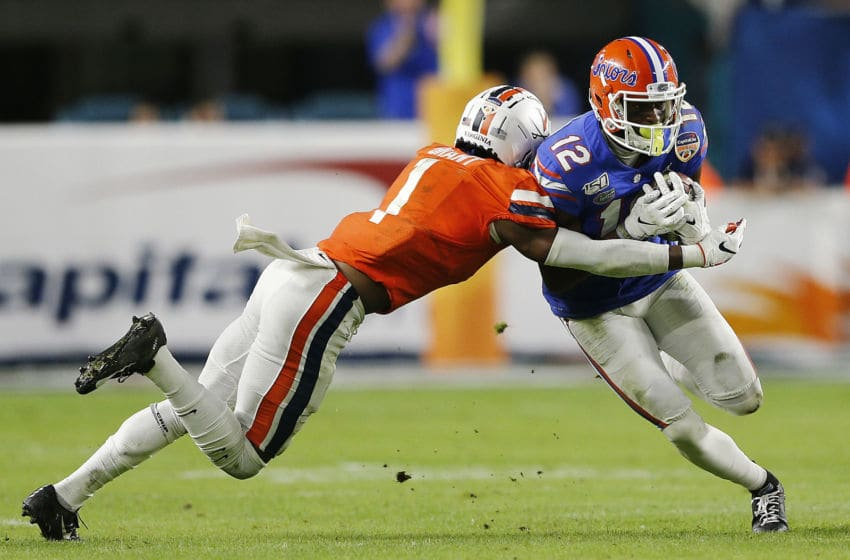 MIAMI, FLORIDA - DECEMBER 30: Van Jefferson #12 of the Florida Gators breaks a tackle from Nick Grant #1 of the Virginia Cavaliers during the first half of the Capital One Orange Bowl at Hard Rock Stadium on December 30, 2019 in Miami, Florida. (Photo by Michael Reaves/Getty Images)