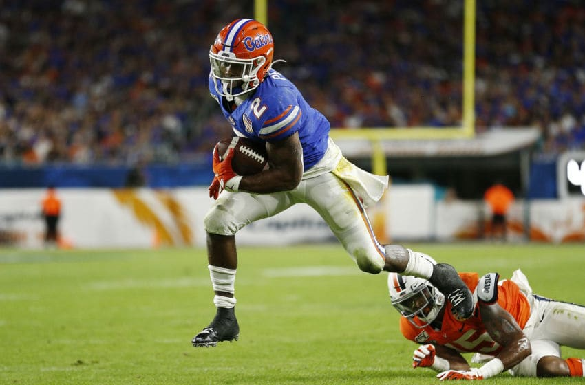 MIAMI, FLORIDA - DECEMBER 30: Lamical Perine #2 of the Florida Gators breaks a tackle by De'Vante Cross #15 of the Virginia Cavaliers to run for a touchdown during the first half of the Capital One Orange Bowl at Hard Rock Stadium on December 30, 2019 in Miami, Florida. (Photo by Michael Reaves/Getty Images)