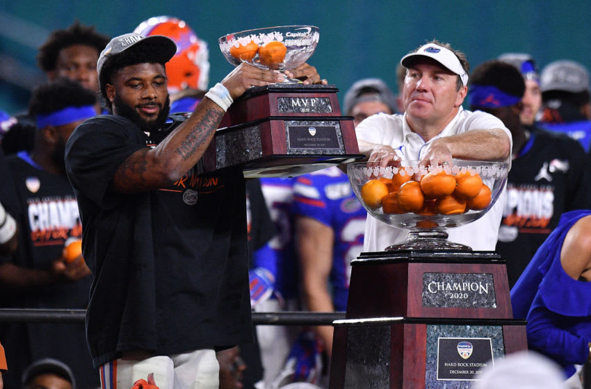 MIAMI, FLORIDA - DECEMBER 30: Lamical Perine #2 raises the MVP Trophy and Head Coach Dan Mullen of the Florida Gators celebrates after winning the Capital One Orange Bowl against the Virginia Cavaliers at Hard Rock Stadium on December 30, 2019 in Miami, Florida. (Photo by Mark Brown/Getty Images)
