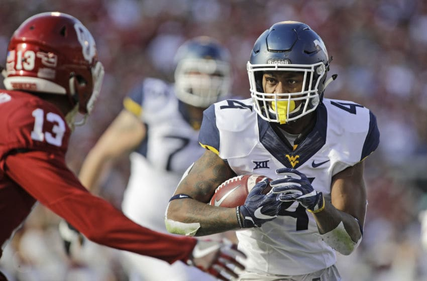 NORMAN, OK - NOVEMBER 25: Running back Kennedy McKoy #4 of the West Virginia Mountaineers looks to get around cornerback Tre Norwood #13 of the Oklahoma Sooners at Gaylord Family Oklahoma Memorial Stadium on November 25, 2017 in Norman, Oklahoma. Oklahoma defeated West Virginia 59-31. (Photo by Brett Deering/Getty Images)