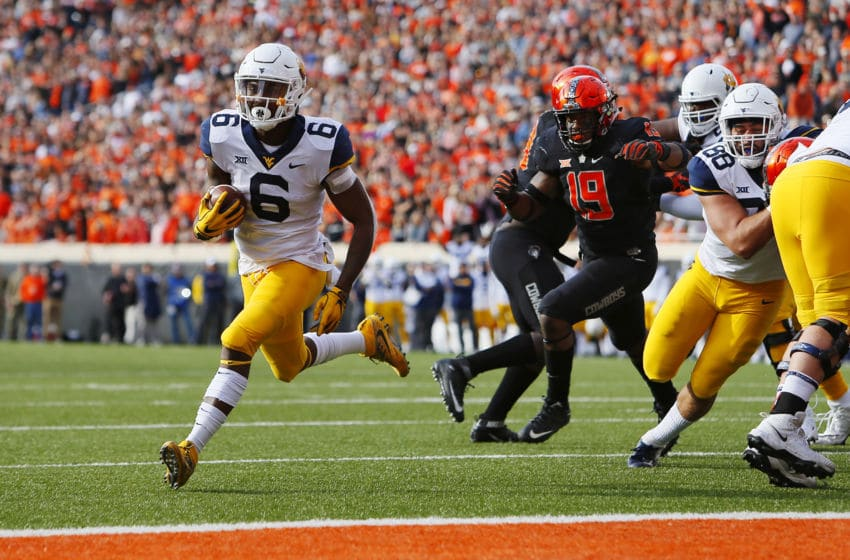 STILLWATER, OK - NOVEMBER 17: Running back Kennedy McKoy #6 of the West Virginia Mountaineers slips through a gap to score a touchdown against the Oklahoma State Cowboys in the first quarter on November 17, 2018 at Boone Pickens Stadium in Stillwater, Oklahoma. (Photo by Brian Bahr/Getty Images)