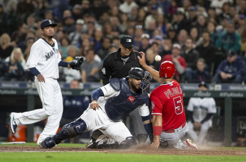 SEATTLE, WA - APRIL 01: Omar Narvaez #22 of the Seattle Mariners loses the ball in an error as he collides with Albert Pujols #5 of the Los Angeles Angels of Anaheim, who is safe at home in the fifth inning at T-Mobile Park on April 1, 2019 in Seattle, Washington. (Photo by Lindsey Wasson/Getty Images)