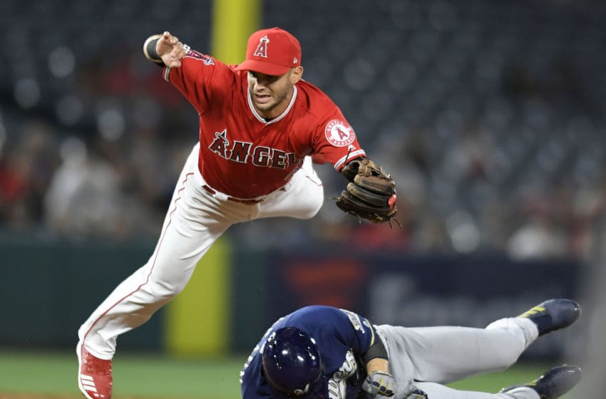 ANAHEIM, CA - APRIL 10: Tommy La Stella #9 of the Los Angeles Angels of Anaheim leaps over Ryan Braun #8 of the Milwaukee Brewers at second base to complete the throw for the double play at first in the fifth inning at Angel Stadium of Anaheim on April 10, 2019 in Anaheim, California. (Photo by John McCoy/Getty Images)