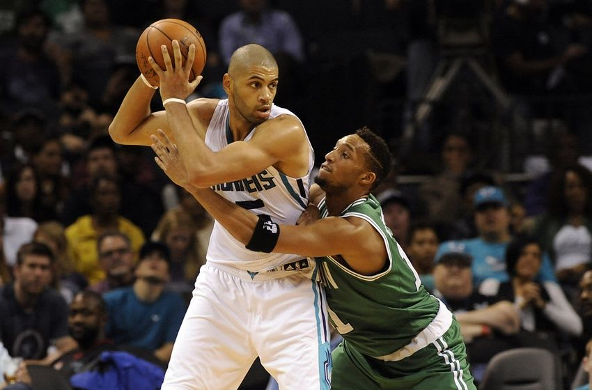 Dec 23, 2015; Charlotte, NC, USA; Charlotte Hornets guard Nicolas Batum (5) passes the ball as he is defended by Boston Celtics guard forward Evan Turner (11) during the second half of the game at Time Warner Cable Arena. Celtics win 102-89. Mandatory Credit: Sam Sharpe-USA TODAY Sports
