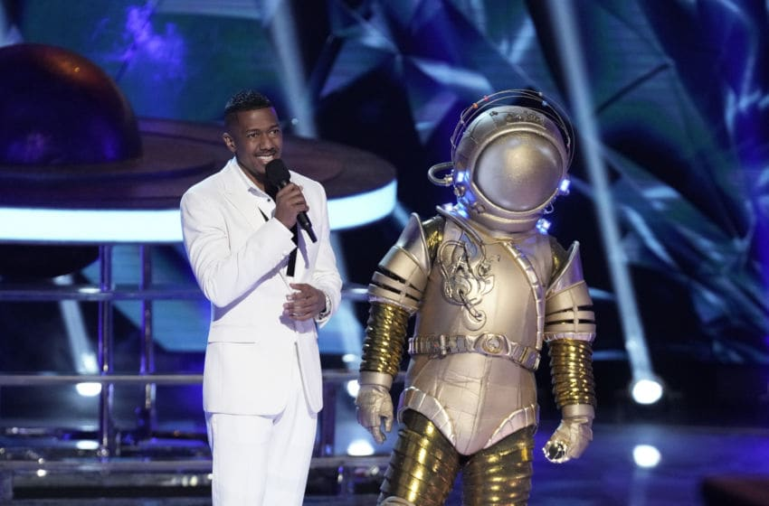 """THE MASKED SINGER: L-R: Host Nick Cannon and The Astronaut in the """"Old Friends, New Clues: Group C Championships"""" episode of THE MASKED SINGER airing Wednesday, March 25 (8:00-9:01 PM ET/PT) on FOX.. CR: Michael Becker / FOX. © 2020 FOX Media LLC."""