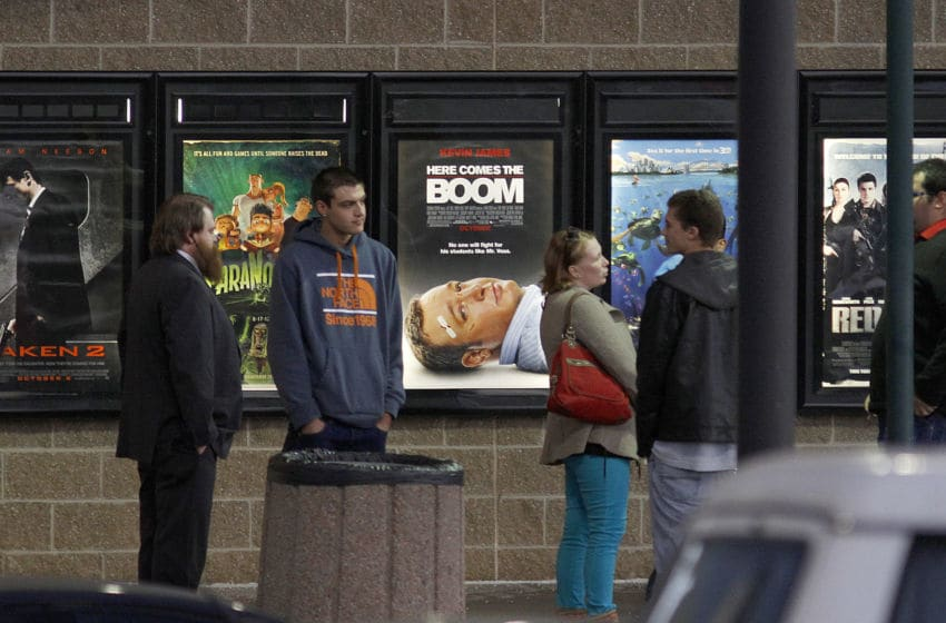 AURORA, CO - JANUARY 17: Invited guests stand by a line of movie posters before making their way into a reopening ceremony for the Cinemark Century 16 Theaters on January 17, 2013 in Aurora, Colorado. The theater was the site of a mass shooting on July 20, 2012 that killed 12 people and wounded dozens of others. (Photo by Marc Piscotty/Getty Images)