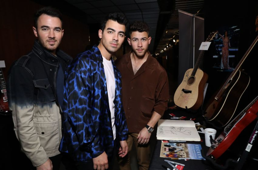 LOS ANGELES, CALIFORNIA - JANUARY 23: (L-R) Kevin Jonas, Joe Jonas, and Nick Jonas of Jonas Brothers with the GRAMMY Charities Signings during the 62nd Annual GRAMMY Awards at STAPLES Center on January 23, 2020 in Los Angeles, California. (Photo by Robin Marchant/Getty Images for The Recording Academy)