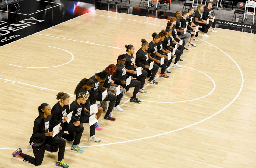 PALMETTO, FLORIDA - AUGUST 28: Connecticut Sun players and staff take a knee holding signs with a quote from Martin Luther King, Jr. during the National Anthem prior to the game against the Los Angeles Sparks at Feld Entertainment Center on August 28, 2020 in Palmetto, Florida. NOTE TO USER: User expressly acknowledges and agrees that, by downloading and or using this photograph, User is consenting to the terms and conditions of the Getty Images License Agreement. (Photo by Douglas P. DeFelice/Getty Images)