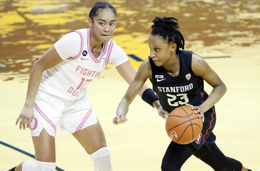 EUGENE, OREGON - FEBRUARY 15: Kiana Williams #23 of the Stanford Cardinal dribbles the ball as Te-Hina Paopao #12 of the Oregon Ducks defends during the first half at Matthew Knight Arena on February 15, 2021 in Eugene, Oregon. (Photo by Soobum Im/Getty Images)
