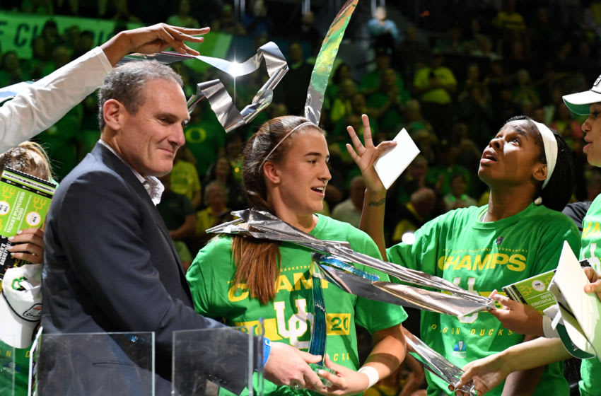 LAS VEGAS, NEVADA - MARCH 08: (L-R) Pac-12 Commissioner Larry Scott presents the Most Outstanding Player award to Sabrina Ionescu #20 of the Oregon Ducks as Ruthy Hebard #24 looks on while streamers fall from the rafters after the Ducks defeated the Stanford Cardinal 89-56 to win the championship game of the Pac-12 Conference women's basketball tournament at the Mandalay Bay Events Center on March 8, 2020 in Las Vegas, Nevada. (Photo by Ethan Miller/Getty Images)