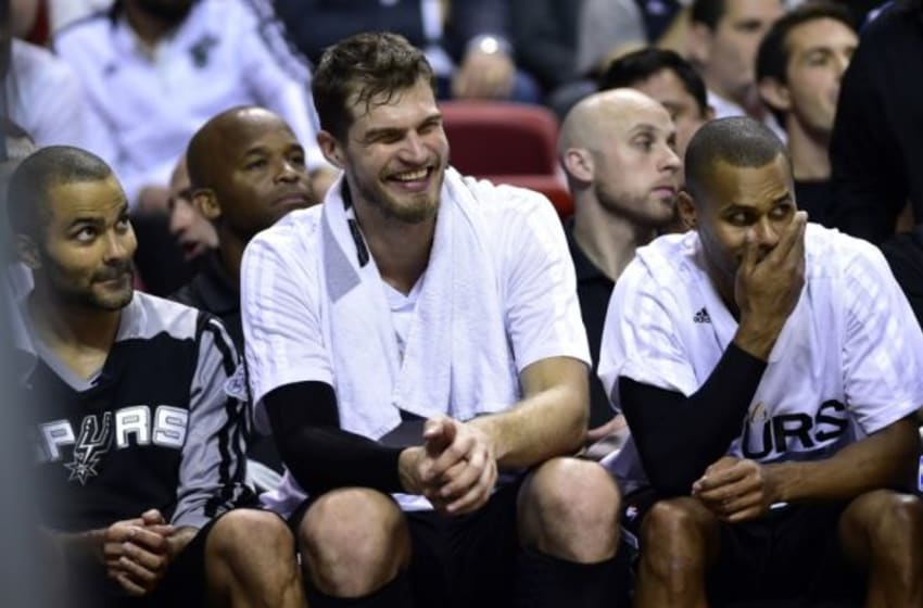 Jun 12, 2014; Miami, FL, USA; San Antonio Spurs guard Tony Parker (left) and center Tiago Splitter (center) and guard Patty Mills (right) react during the fourth quarter of game four of the 2014 NBA Finals against the Miami Heat at American Airlines Arena. San Antonio Spurs won 107-86. Mandatory Credit: Bob Donnan-USA TODAY Sports