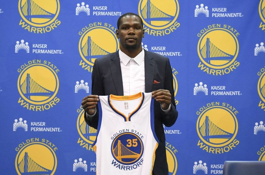 Jul 7, 2016; Oakland, CA, USA; Kevin Durant poses for a photo with his jersey during a press conference after signing with the Golden State Warriors at the Warriors Practice Facility. Mandatory Credit: Kyle Terada-USA TODAY Sports
