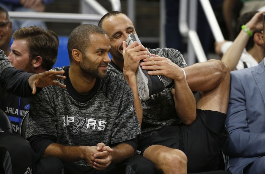 Oct 12, 2016; Orlando, FL, USA; San Antonio Spurs guard Manu Ginobili (20) smell his shoe as guard Tony Parker (9) smiles from the bench against the Orlando Magic during the first quarter at Amway Center. Mandatory Credit: Kim Klement-USA TODAY Sports