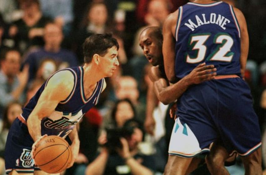 SEATTLE, UNITED STATES: Utah Jazz' John Stockton (L) dribbles around a screen set by teammate Karl Malone (R) on Seattle Supersonic Gary Payton (C) during fourth quarter action of their game in Seattle, WA, 24 March, 2000. Stockton scored two points off of the screen as Utah went to win 98-95. AFP PHOTO Dan LEVINE (Photo credit should read DAN LEVINE/AFP/Getty Images)