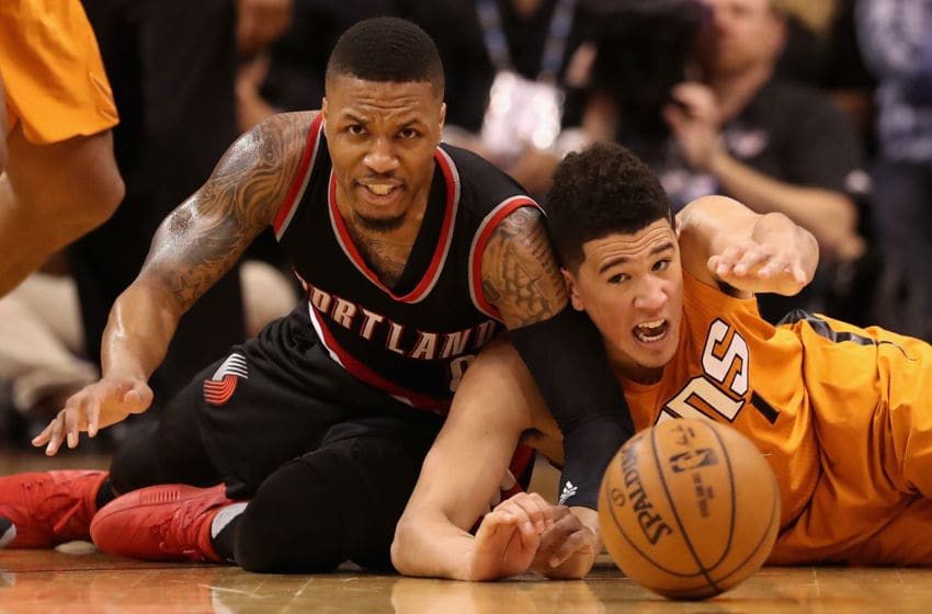 PHOENIX, AZ - MARCH 12: Damian Lillard #0 of the Portland Trail Blazers and Devin Booker #1 of the Phoenix Suns reach for a loose ball during the second half of the NBA game at Talking Stick Resort Arena on March 12, 2017 in Phoenix, Arizona. The Trailblazers defeated the Suns 110-101. NOTE TO USER: User expressly acknowledges and agrees that, by downloading and or using this photograph, User is consenting to the terms and conditions of the Getty Images License Agreement. (Photo by Christian Petersen/Getty Images)