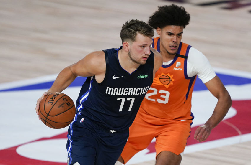 LAKE BUENA VISTA, FLORIDA - AUGUST 02: Luka Doncic #77 of the Dallas Mavericks drives against Cameron Johnson #23 of the Phoenix Suns during the first half at Visa Athletic Center at ESPN Wide World Of Sports Complex on August 2, 2020 in Lake Buena Vista, Florida. NOTE TO USER: User expressly acknowledges and agrees that, by downloading and or using this photograph, User is consenting to the terms and conditions of the Getty Images License Agreement. (Photo by Ashley Landis-Pool/Getty Images)