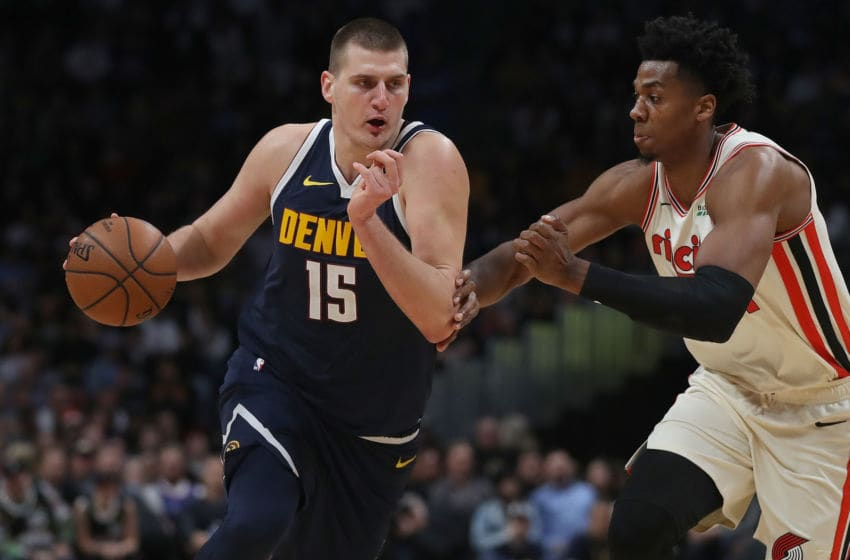 DENVER, COLORADO - DECEMBER 12: Nikola Jokic #15 of the Denver Nuggets drives to the basket against Hassan Whiteside #21 of the Portland Trail Blazers in the fourth quarter at the Pepsi Center on December 12, 2019 in Denver, Colorado. NOTE TO USER: User expressly acknowledges and agrees that, by downloading and or using this photograph, User is consenting to the terms and conditions of the Getty Images License Agreement. (Photo by Matthew Stockman/Getty Images)