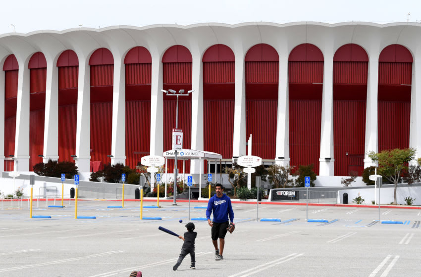 INGLEWOOD, CALIFORNIA - MARCH 31: A father and son play baseball, amidst the COVID-19 pandemic, in front of The Forum, which was recently purchased by owner Steve Ballmer of the Los Angeles Clippers on March 31, 2020 in Inglewood, California. (Photo by Harry How/Getty Images)