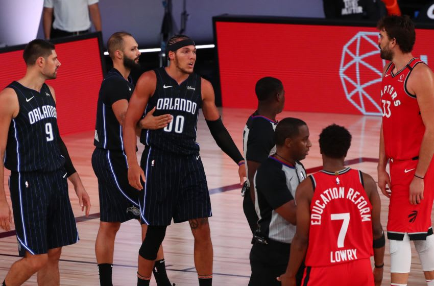 LAKE BUENA VISTA, FLORIDA - AUGUST 05: Aaron Gordon #00 of the Orlando Magic is held back by Evan Fournier (10) after being fouled by Kyle Lowry #7 of the Toronto Raptors in the second half at Visa Athletic Center at ESPN Wide World Of Sports Complex on August 5, 2020 in Lake Buena Vista, Florida. NOTE TO USER: User expressly acknowledges and agrees that, by downloading and or using this photograph, User is consenting to the terms and conditions of the Getty Images License Agreement. (Photo by Kim Klement-Pool/Getty Images)