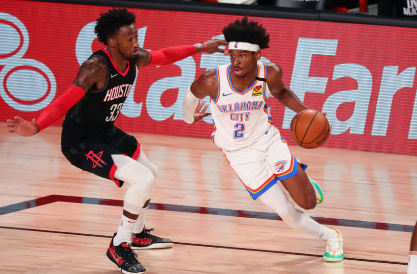 LAKE BUENA VISTA, FLORIDA - AUGUST 24: Shai Gilgeous-Alexander #2 of the Oklahoma City Thunder drives against Robert Covington #33 of the Houston Rockets during the first half of game four of the first round of the 2020 NBA Playoffs at AdventHealth Arena at ESPN Wide World Of Sports Complex on August 24, 2020 in Lake Buena Vista, Florida. NOTE TO USER: User expressly acknowledges and agrees that, by downloading and or using this photograph, User is consenting to the terms and conditions of the Getty Images License Agreement. (Photo by Kim Klement-Pool/Getty Images)