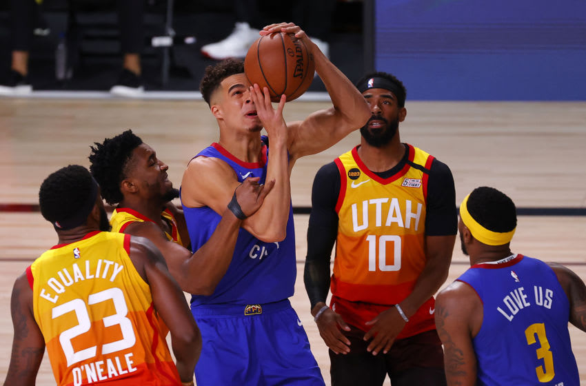 LAKE BUENA VISTA, FLORIDA - AUGUST 08: Donovan Mitchell #45 of the Utah Jazz fouls Michael Porter Jr. #1 of the Denver Nuggets during the first quarter at The Arena at ESPN Wide World Of Sports Complex on August 08, 2020 in Lake Buena Vista, Florida. NOTE TO USER: User expressly acknowledges and agrees that, by downloading and or using this photograph, User is consenting to the terms and conditions of the Getty Images License Agreement. (Photo by Kevin C. Cox/Getty Images)