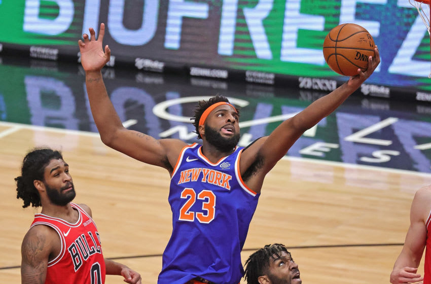 CHICAGO, ILLINOIS - FEBRUARY 01: Mitchell Robinson #23 of the New York Knicks rebounds over Patrick Williams #9 and Coby White #0 of the Chicago Bulls at the United Center on February 01, 2021 in Chicago, Illinois. NOTE TO USER: User expressly acknowledges and agrees that, by downloading and or using this photograph, User is consenting to the terms and conditions of the Getty Images License Agreement. (Photo by Jonathan Daniel/Getty Images)