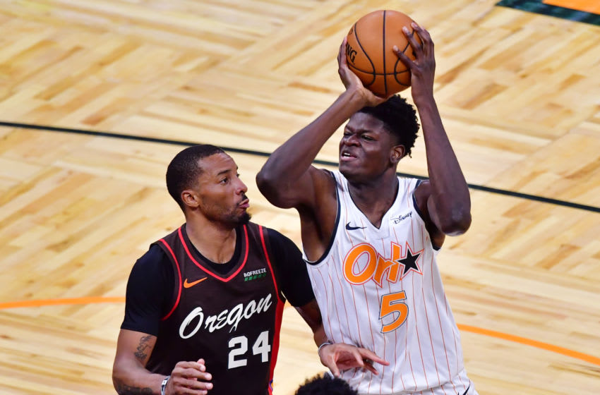 ORLANDO, FLORIDA - MARCH 26: Mo Bamba #5 of the Orlando Magic looks to shoot against Norman Powell #24 of the Portland Trail Blazers in the first half at Amway Center on March 26, 2021 in Orlando, Florida. NOTE TO USER: User expressly acknowledges and agrees that, by downloading and or using this photograph, User is consenting to the terms and conditions of the Getty Images License Agreement. (Photo by Julio Aguilar/Getty Images)