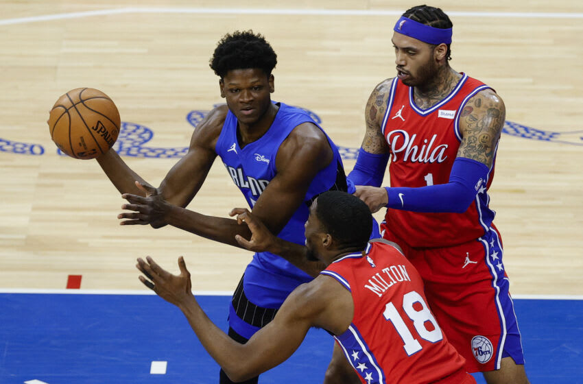 PHILADELPHIA, PENNSYLVANIA - MAY 14: Mo Bamba #5 of the Orlando Magic is guarded by Shake Milton #18 and Mike Scott #1 of the Philadelphia 76ers during the fourth quarter at Wells Fargo Center on May 14, 2021 in Philadelphia, Pennsylvania. NOTE TO USER: User expressly acknowledges and agrees that, by downloading and or using this photograph, User is consenting to the terms and conditions of the Getty Images License Agreement. (Photo by Tim Nwachukwu/Getty Images)