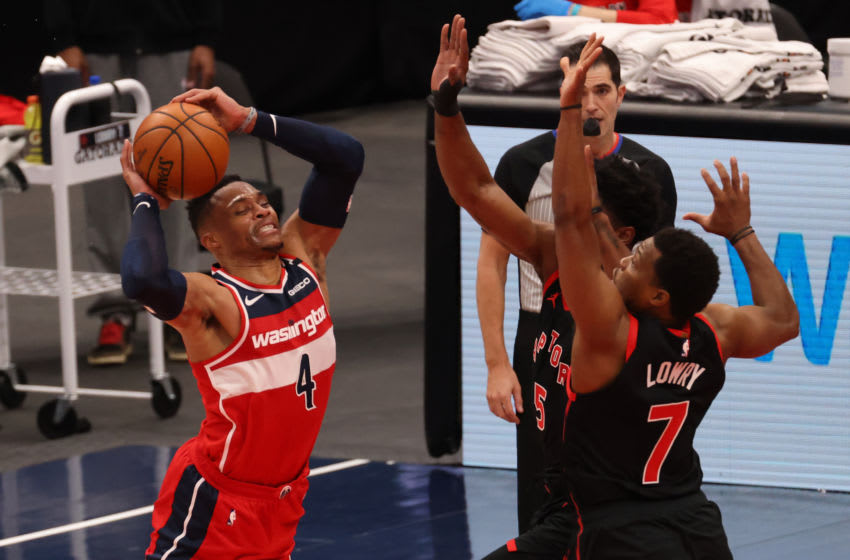 Feb 10, 2021; Washington, District of Columbia, USA; Washington Wizards guard Russell Westbrook (4) leaps to pass the ball as Toronto Raptors guard Kyle Lowry (7) defends in the third quarter at Capital One Arena. Mandatory Credit: Geoff Burke-USA TODAY Sports