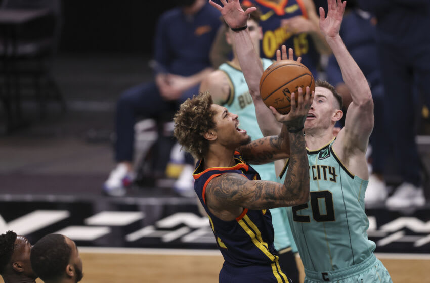 Feb 20, 2021; Charlotte, North Carolina, USA; Golden State Warriors guard Kelly Oubre Jr., left, drives to the basket against Charlotte Hornets forward Gordon Hayward (20) during the first half at Spectrum Center. Mandatory Credit: Nell Redmond-USA TODAY Sports