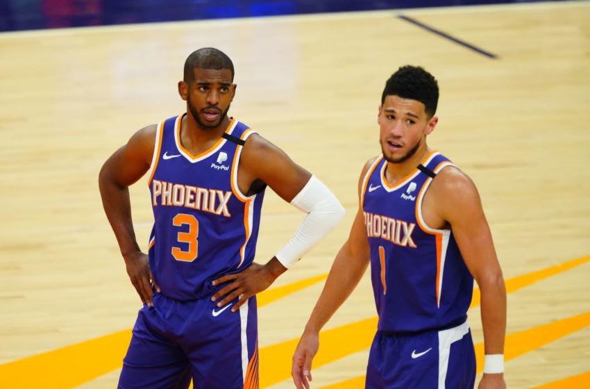Apr 13, 2021; Phoenix, Arizona, USA; Phoenix Suns guard Chris Paul (3) and Devin Booker (1) against the Miami Heat in the second half at Phoenix Suns Arena. Mandatory Credit: Mark J. Rebilas-USA TODAY Sports
