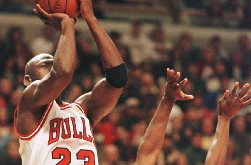 Michael Jordan (L) of the Chicago Bulls shoots over Calbert Chaney of the Washington Bullets 27 April 1997 during the first half of game two of their first round playoff game at the United Center in Chicago,IL. Jordan scored 55 points to lead the Bulls to a 109-104 victroy over the Bullets. AFP PHOTO Jeff HAYNES (Photo by JEFF HAYNES / AFP) (Photo credit should read JEFF HAYNES/AFP via Getty Images)