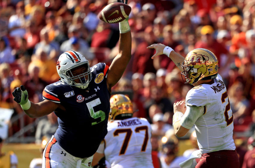 TAMPA, FLORIDA - JANUARY 01: Tanner Morgan #2 of the Minnesota Golden Gophers is rushed by Derrick Brown #5 of the Auburn Tigers during the 2020 Outback Bowl at Raymond James Stadium on January 01, 2020 in Tampa, Florida. (Photo by Mike Ehrmann/Getty Images)